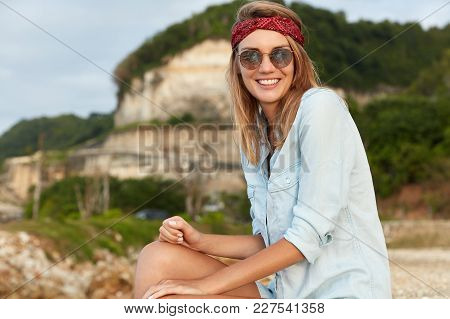 Glad Female Model In Headband And Sunglasses Sits At Top Of Cliff, Being In High Spirit, Feels Freed