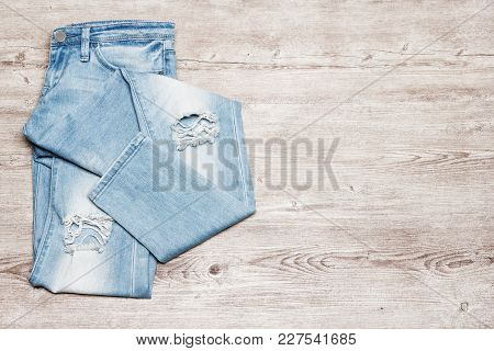 Women Ripped Skinny Blue Jeans On Shabby Wooden Surface, Top View. Fashion & Style Minimal Backgroun
