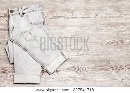Ripped Torn Jeans On Shabby Wooden Surface, Top View. Fashion & Style Minimal Background, Free Space