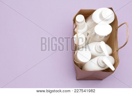 Paper Bag Filled With Various Cosmetic Products, Top View. Beauty Shopping Concept, Copy Space