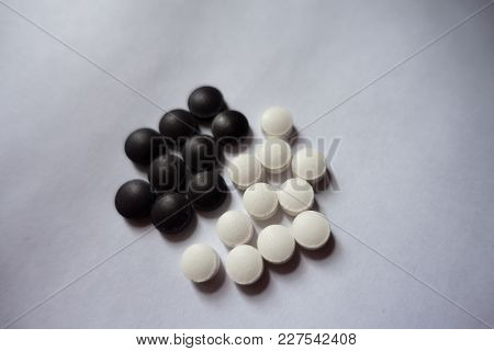 Black Tablets Of Bilberry And White Ones Of Vitamin K2