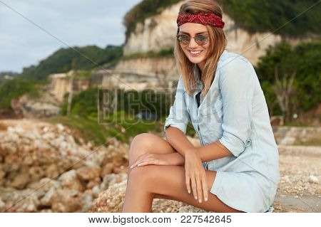 Outdoor Shot Of Pretty Female Wears Sunglasses, Red Headband And Loose T Shirt, Looks Happily Down,