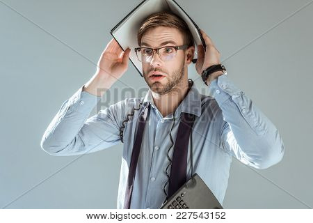 Young Surprised Businessman Holding Notebook On His Head Isolated On Grey