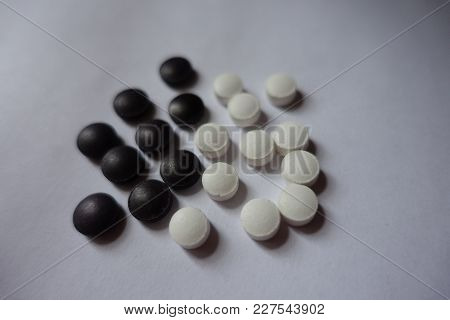 White And Black Round Tablets Of Nutritional Supplements