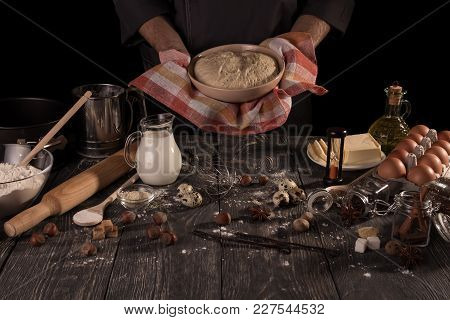 Ingredients For Baking And Ready-made Dough In Bowl, In The Hands Of Baker