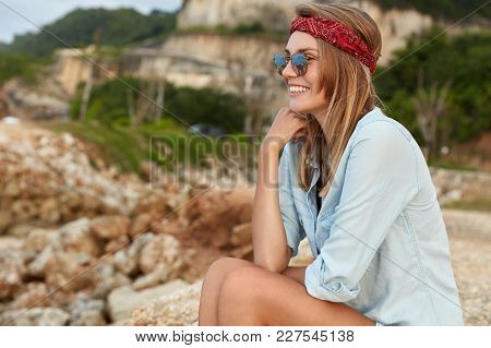 Portrait Of Cheerful Young Female Has Hiking Tour In Mountains, Poses At Camera With Cheerful Expres