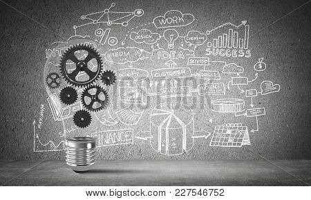 Lightbulb With Multiple Gears Inside Placed Against Business-plan Information Sketched On Grey Wall.