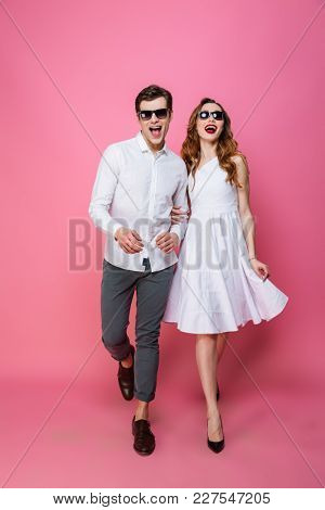 Full-length photo of modern fascinating lady and guy trendy dressed walking together on camera olated over pink background