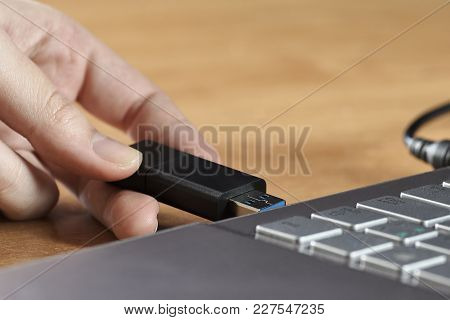 A Female Hand Holding A Usb Flash Drive Before The Silver Laptop