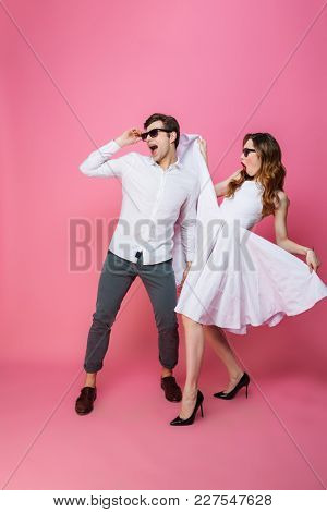 Full-length image of joyful artistic lady and guy in white clothing dancing and partying while homecoming isolated over pink background