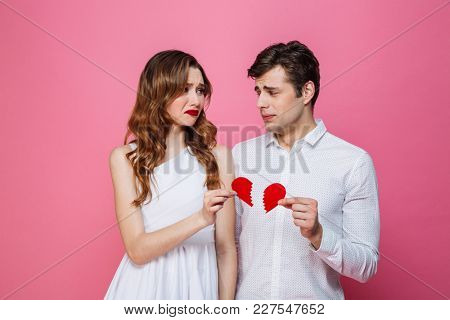 Portrait of an upset smartly dressed couple holding two pieces of a broken heart isolated over pink background