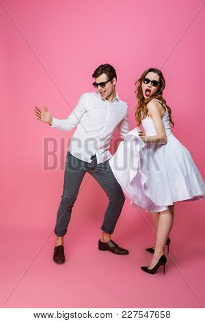 Full-length image of modern artistic girl and guy in white clothing dancing and partying while homecoming isolated over pink background