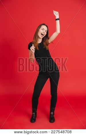 Full-length photo of joyous woman 20s wearing black t-shirt singing and dancing with pleasure isolated over red background
