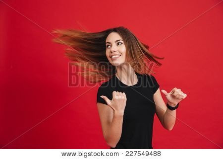 Image of energetic woman with flowing brown hair showing fingers backwards on copyspace isolated over red background