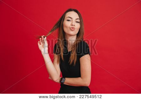 Image of beautiful woman with long brown hair touching brown strand playfully and putting lips for kissing isolated over red background