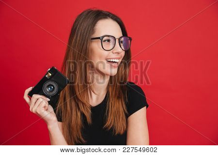 Image of joyous adult girl wearing black t-shirt and eyeglasses with retro camera in hand smiling and looking aside isolated over red background