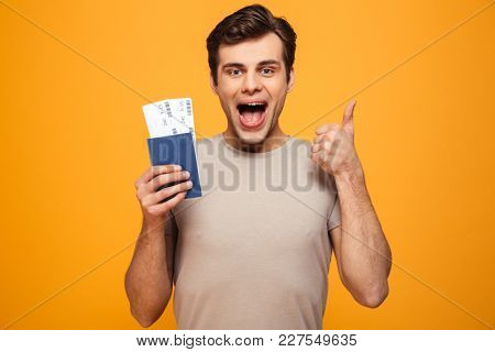 Portrait of a joyful young man holding passport with flying tickets and showing thumbs up isolated over yellow background