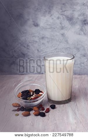 A Glass Of Milk And Mix Of Seeds In Glass Bowl. Almonds, Raisins, Pumpkin Seeds, Sunflower Seeds, Wa