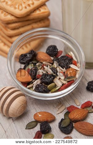 Mix Of Healthy Nuts And Dried Fruits On Rustic Wooden Background. Glass Of Milk And Biscuits. Wooden