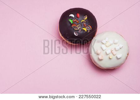 Doughnuts With Chocolate And White Icing On Pastel Pink Background. Sweet Dessert Donuts
