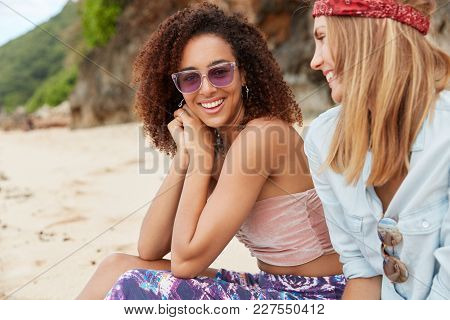 Outdoor Shot Of Two Mixed Race Female Lesbians Have Pleasant Talk During Recreation At Sandy Beach.
