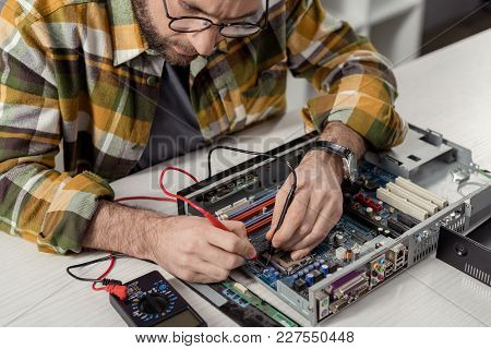 Cropped Image Repairman Using Multimeter While Fixing Computer Motherboard