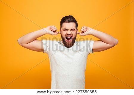 Portrait of an annoyed bearded man covering ears and screaming isolated over yellow background