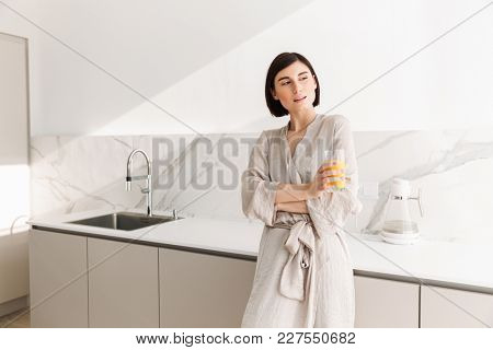 Young fascinating woman with short dark hair standing in kitchen and drinking fresh orange juice from transparent glass