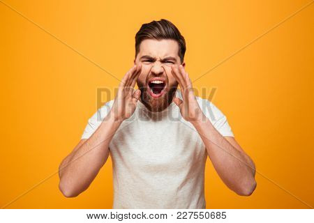 Portrait of a mad bearded man shouting isolated over yellow background