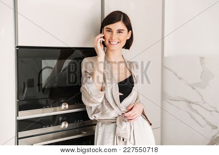 Photo of smiling woman with short dark hair wearing sexual robe posing in kitchen and speaking on mobile phone