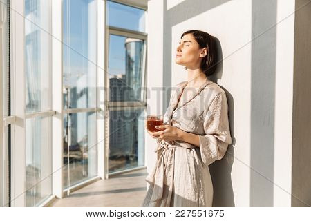 Elegant woman with short dark hair in housecoat holding glass of tea and enjoying sunny weather while standing near window in posh apartment