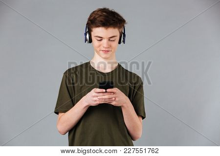 Portrait of a smiling male teenager wearing t-shirt listening to music with headphones while standing and using mobile phone isolated over gray background