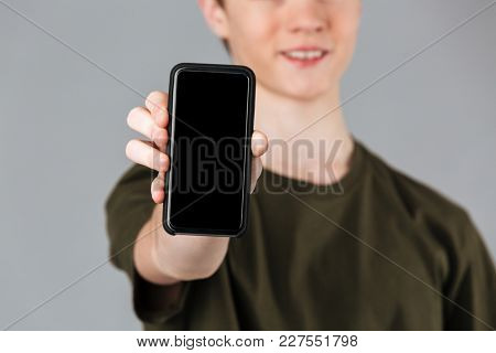 Close up of a smiling male teenager showing blank screen mobile phone isolated over gray background