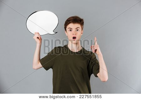 Portrait of a surprised male teenager wearing t-shirt holding blank speech bubble and pointing finger up isolated over gray background