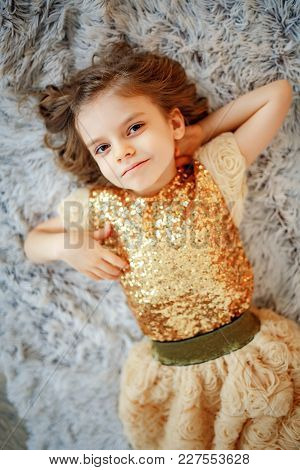 From Above Little Girl In Glittering Golden Dress Lying On Fur And Looking At Camera.
