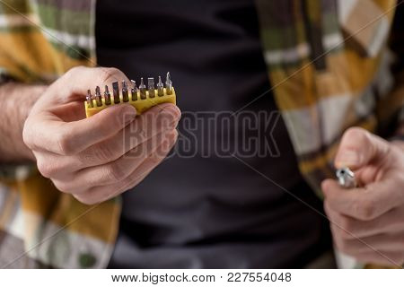 Cropped Image Of Hands Holding Screwdriver And Its Attachments