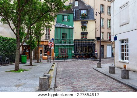 View of small cobblestone street with little bar, shops and typical architecture in Paris, France.