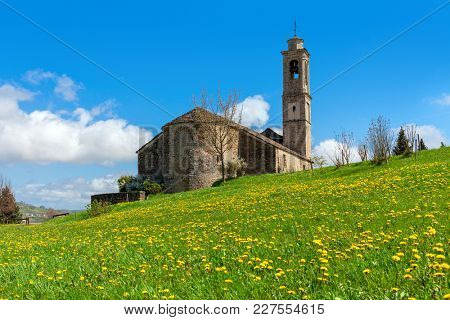 Old medieval church on the meadow with green grass and yellow flowers under blue sky in Piedmont, Northern Italy.