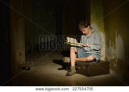 Lonely Little Boy Reading Book  In A Dark Cellar