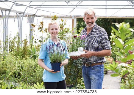 Portrait Of Male Customer With Sales Assistant At Garden Center