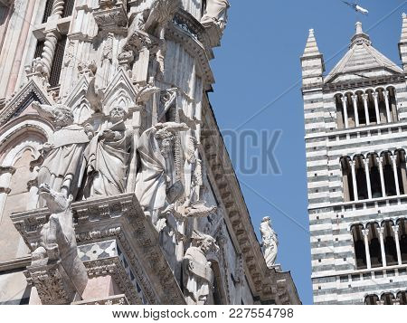 Exterior Of Siena Cathedral With Scupltutes Of Philosophers Next To The Black And White Striped Bell