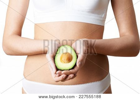 Close Up Of Woman In Underwear Holding Halved Avocado