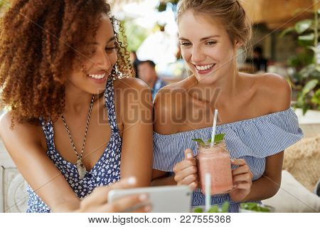 Portrait Of European And African Females Lesbians Watch Interesting Movie On Mobile Phone, Enjoy Wir