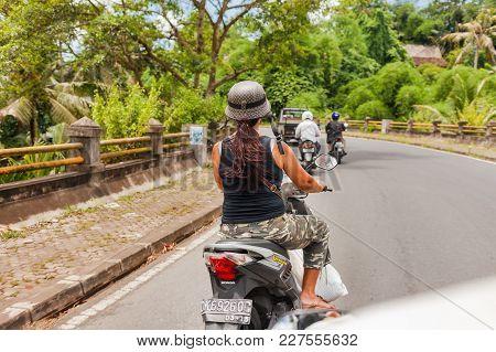 Ubud, Indonesia - January 30, 2013. Woman In Unfastened Fashionable Helmet Driving Bike.
