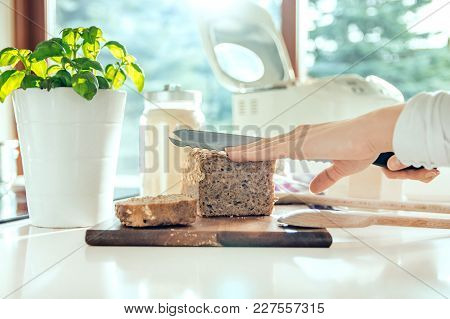 Woman's Hand With Kitchen Knife Cutting Homemade Healthy Bread. Photo Taken In The Light Of Natural