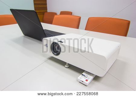 Projector Connected To Laptop For Presentation On White Table In A Meeting Room , Business Concept.