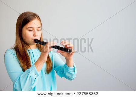A Portrait Of A Girl Plaing Flute