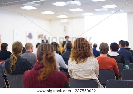 Speakers Giving A Talk At Business Meeting. Audience In The Conference Hall. Rear View. Business And