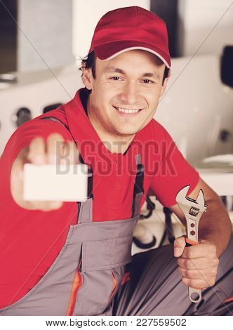 Plumber Is Holding A Spanner In Hand And Showing Business Card.