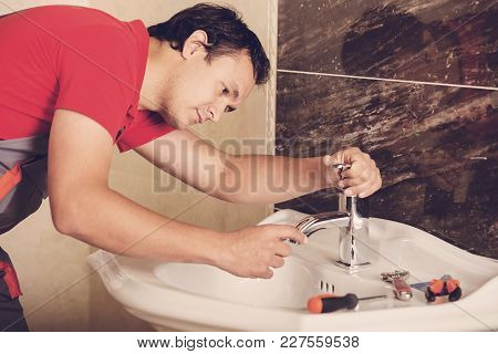 Plumber Is Repairing A Faucet With Water In The Bathroom